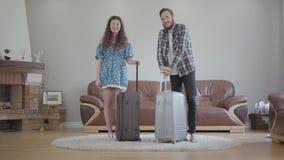 Retrato de la situaci?n smilling feliz de los pares con las maletas grandes en casa El hombre barbudo joven y la muchacha hermosa metrajes