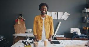 Retrato de la situación sonriente del diseñador afroamericano hermoso en el trabajo almacen de video