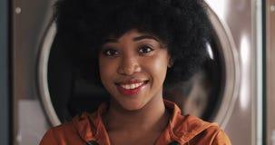 Retrato de la situaci?n afroamericana sonriente joven de la mujer en el lavadero p?blico del autoservicio almacen de metraje de vídeo