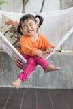 Retrato de la sonrisa dentuda de los niños y de la relajación en crad de la ropa Foto de archivo