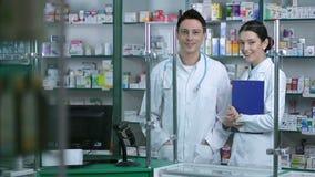 Retrato de la sonrisa experimentada del equipo de los farmacéuticos almacen de metraje de vídeo