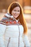 Retrato de la sonrisa hermosa woan en abajo la chaqueta blanca en luz del sol Imágenes de archivo libres de regalías