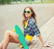 Retrato de la sonrisa muchacha bastante fresca en gafas de sol con el patín Foto de archivo