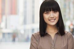 Retrato de la sonrisa, mujer confiada, joven con explosiones y pelo largo, al aire libre en Pekín, China Imagen de archivo