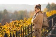Retrato de la sonrisa y de la mirada abajo de mujer en otoño al aire libre Fotos de archivo