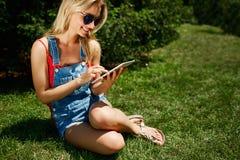 Retrato de la tableta blondy joven feliz del uso del estudiante universitario de la mujer imágenes de archivo libres de regalías