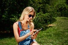 Retrato de la tableta rubia joven feliz del uso del estudiante universitario de la mujer imágenes de archivo libres de regalías