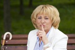 Retrato de la vieja mujer rubia con el finger en los labios Imagen de archivo