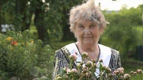Retrato de la vieja mujer sonriente en el parque metrajes