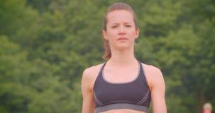 Retrato de la vista delantera del primer del basculador femenino deportivo bonito joven que camina en el puente con la gente en e almacen de video