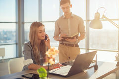 Retrato de la vista lateral de colegas en la oficina espaciosa ligera ocupada durante día laborable Horario del planeamiento de l Imágenes de archivo libres de regalías