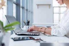 Retrato de la vista lateral de la mujer que trabaja en hogar-oficina como Internet del teletrabajador, el mecanografiar y el prac fotografía de archivo libre de regalías