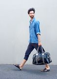 Retrato de la vista lateral de un hombre joven que camina con el bolso del viaje Fotografía de archivo
