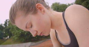Retrato de la vista lateral del primer del basculador femenino deportivo caucásico joven que es sentada agotada en el banco en ci almacen de metraje de vídeo