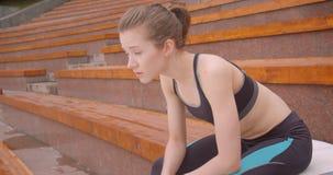 Retrato de la vista lateral del primer del basculador femenino deportivo caucásico joven que es sentada cansada en el banco en ci metrajes