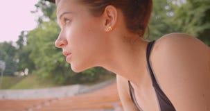 Retrato de la vista lateral del primer del basculador femenino deportivo caucásico joven que es sentada de reclinación agotada en almacen de metraje de vídeo