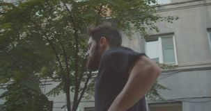 Retrato de la vista lateral del primer del corredor masculino deportivo caucásico adulto que activa abajo de la calle en la ciuda almacen de metraje de vídeo