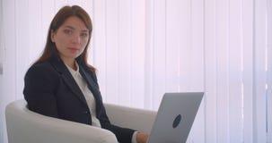 Retrato de la vista lateral del primer de la empresaria acertada joven usando el ordenador portátil que mira la cámara que sonríe metrajes