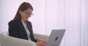 Retrato de la vista lateral del primer de la empresaria caucásica joven en vidrios usando el ordenador portátil que mira la sonri almacen de metraje de vídeo