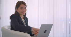 Retrato de la vista lateral del primer de la empresaria caucásica joven usando el ordenador portátil que mira la cámara que sonrí almacen de metraje de vídeo