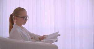 Retrato de la vista lateral del primer de la empresaria rubia caucásica bonita joven en vidrios que lee un libro que mira la cáma almacen de metraje de vídeo