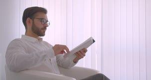 Retrato de la vista lateral del primer del hombre de negocios caucásico barbudo hermoso adulto en vidrios que lee un libro que se almacen de metraje de vídeo