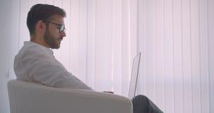 Retrato de la vista lateral del primer del hombre de negocios caucásico barbudo hermoso adulto en vidrios usando el ordenador por metrajes