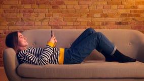 Retrato de la vista lateral del primer de la muchacha bonita joven que usa el teléfono y riendo alegre la mentira en el sofá tran almacen de metraje de vídeo