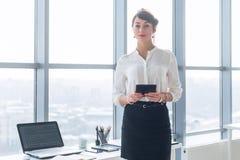Retrato de la vista posterior de un oficinista de sexo femenino joven que usa apps en su tableta, traje formal que lleva, colocán Imágenes de archivo libres de regalías