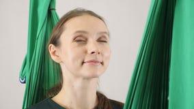 Retrato de la yoga hermosa joven de la mosca feliz, sonriendo, placer Aero- entrenamiento aéreo del instructor de la aptitud de l almacen de metraje de vídeo