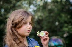 Retrato de las burbujas de jabón de la niña que soplan preciosa linda Foto de archivo