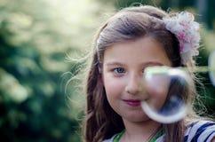 Retrato de las burbujas de jabón de la niña que soplan preciosa linda Fotos de archivo libres de regalías