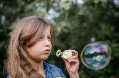 Retrato de las burbujas de jabón de la niña que soplan preciosa linda Imágenes de archivo libres de regalías