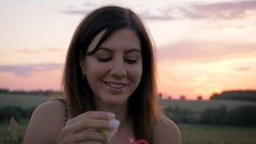 Retrato de las burbujas que soplan sonrientes de la mujer bonita joven por la tarde en la puesta del sol almacen de metraje de vídeo
