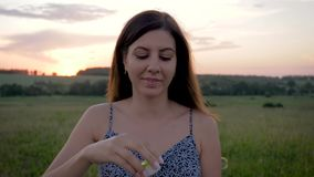 Retrato de las burbujas que soplan sonrientes de la mujer joven de la belleza por la tarde en la puesta del sol almacen de video