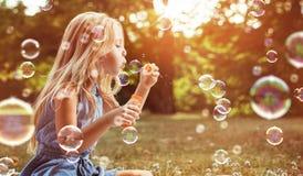 Retrato de las burbujas de un jabón de la muchacha que soplan alegre fotografía de archivo