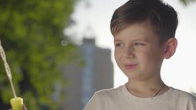 Retrato de las burbujas y de la sonrisa de jabón del muchacho que soplan despreocupado en la cámara en el parque Tiempo lindo del metrajes