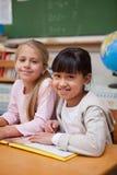 Retrato de las colegialas sonrientes que leen un cuento de hadas Foto de archivo