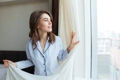 Retrato de las cortinas de la mujer de una ventana felices de abertura foto de archivo