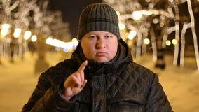 Retrato de las emociones hermosas del hombre del descontento, mostrando una muestra con su finger al aire libre durante noche frí almacen de metraje de vídeo