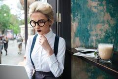 Retrato de las empresarias hermosas jovenes que gozan del café con el ordenador portátil Fotografía de archivo libre de regalías