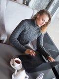 Retrato de las empresarias hermosas jovenes que gozan del café durante trabajo sobre el ordenador portátil portátil, hembra encan Foto de archivo