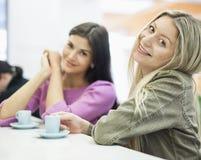 Retrato de las empresarias jovenes que sonríen en la tabla de la cafetería Imágenes de archivo libres de regalías