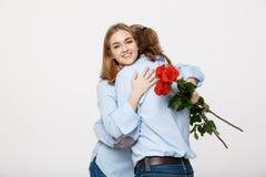 Retrato de las flores de ocultación atractivas de un hombre joven de su novia antes de darle una sorpresa sobre blanco aislada Fotografía de archivo
