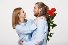 Retrato de las flores de ocultación atractivas de un hombre joven de su novia antes de darle una sorpresa sobre blanco aislada Foto de archivo