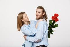 Retrato de las flores de ocultación atractivas de un hombre joven de su novia antes de darle una sorpresa sobre blanco aislada Imágenes de archivo libres de regalías