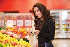 Retrato de las frutas de compra de una mujer joven imagen de archivo