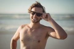 Retrato de las gafas de sol que llevan del hombre descamisado en la playa Imagenes de archivo