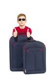 Retrato de las gafas de sol que llevan del muchacho que muestran los pulgares para arriba con viaje Imagenes de archivo