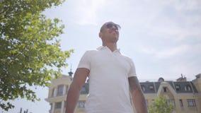 Retrato de las gafas de sol que llevan del hombre de Oriente Medio calvo acertado y de la camiseta blanca Individuo confiado herm almacen de video